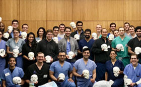 Neurosurgery training session at Tufts Medical Center - students smiling together afterwards.