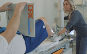 A technician helping Frank as he receives a scan of his knee