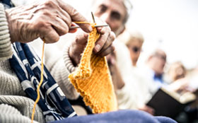 Close up of woman knitting a yellow scarf
