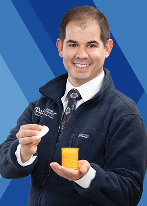 Daniel Migliozzi, RPh, PharmD, BCPS, Clinical Pharmacy Specialist/Kidney Transplant holding a pill bottle