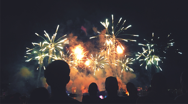Silhouette of individuals watching a fireworks show