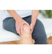 A woman holding her knee in pain