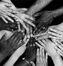 A black and white image of a large group of hands coming together