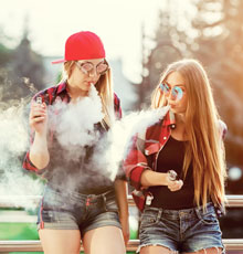 Two female adolescents vaping
