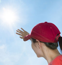 Young girl holding her hand up to block the sun