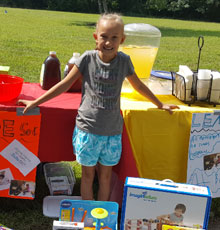 Julia Degnan standing in front of her lemonade stand to raise money for Floating Hospital for Children