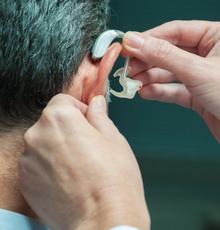 Doctor helping patient place a hearing aid