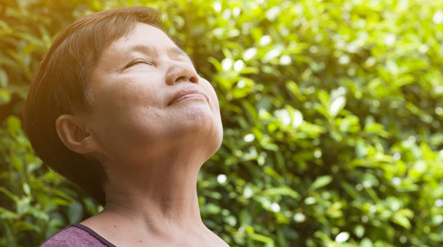 Asian woman breathing in fresh air