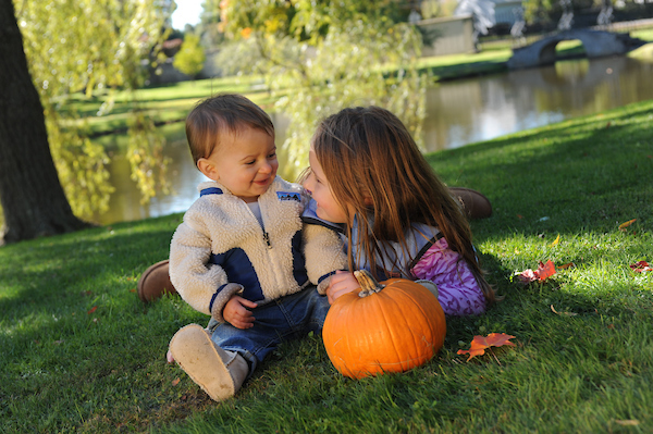 Children at play holding an orange pumpkin outside