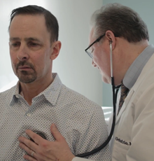 Dr. David DeNofrio listening to a patients heart.