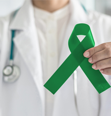 A physician holding a green ribbon for Glaucoma