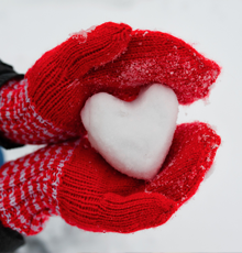 A snow ball shaped like a heart in a person's mittens