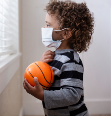 A young boy looking out the window with a basketball in his hand