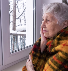An older woman looking out the window at the snow