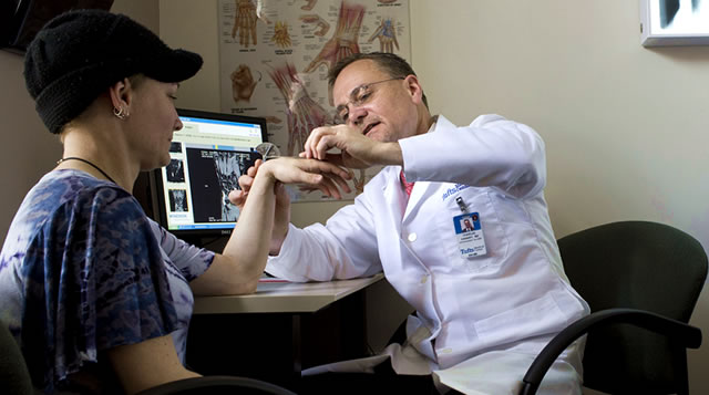 An orthopaedist at Tufts Medical Center examines his patient's hand.