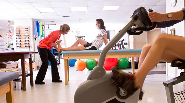 A physical therapist works with her patient at Tufts Medical Center.