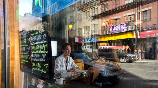 Asian physician sitting in a coffee shop window