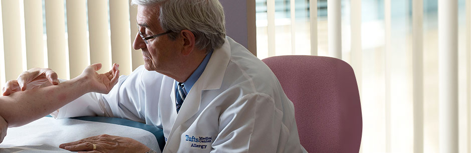 John Ohman, Jr., MD, Chief of the Division of Allergy at Tufts Medical Center examines his patient.