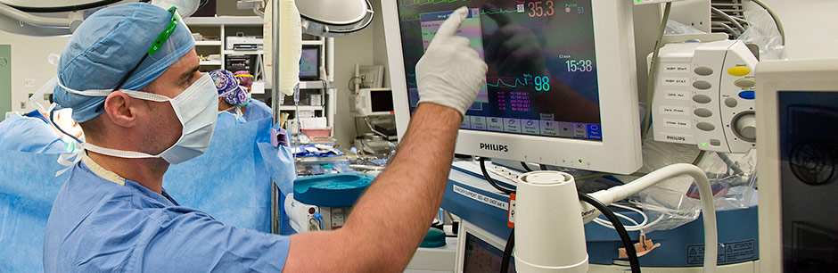 An anesthesiologist at Tufts Medical Center examines a patient's vitals during surgery.