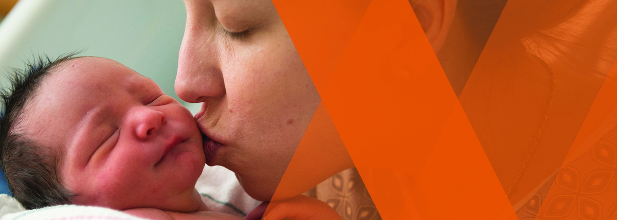 A mother kisses her baby at Tufts Medical Center in Boston.