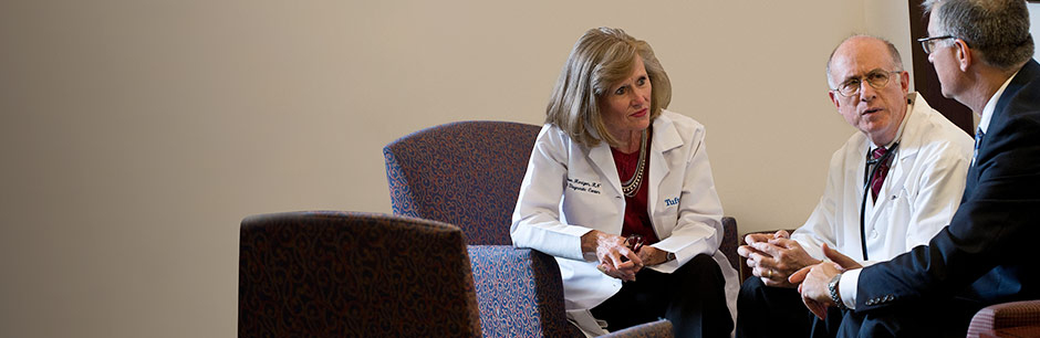 Concierge care doctors in the Pratt Diagnostic Center at Tufts Medical Center talk with their patient.