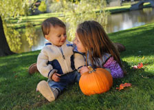 Children at play with an orange pumpkin